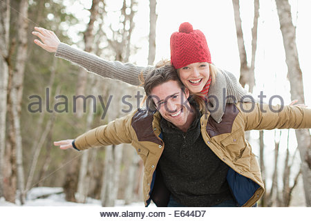 Portrait of smiling couple piggybacking in snow - Stock Photo