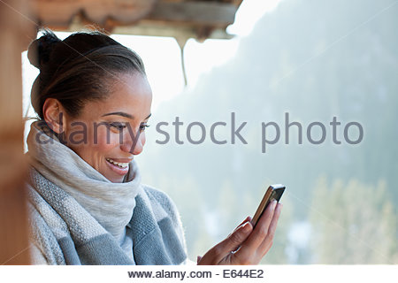 Smiling woman checking cell phone on cabin porch - Stock Photo