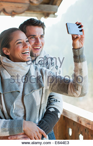 Smiling couple taking self-portrait with camera phone on cabin porch - Stock Photo