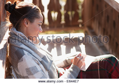 Smiling woman with paper and pen on cabin porch - Stock Photo