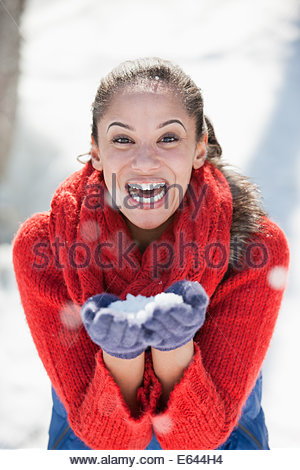 Portrait of woman blowing snow in hands - Stock Photo