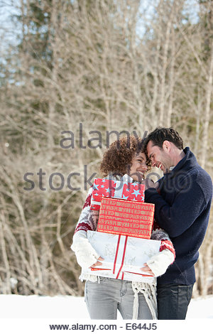 Man and woman with gifts outdoors, winter - Stock Photo