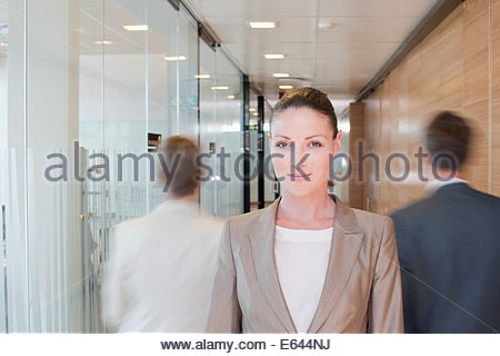 Blurred view of business people walking in office - Stock Photo
