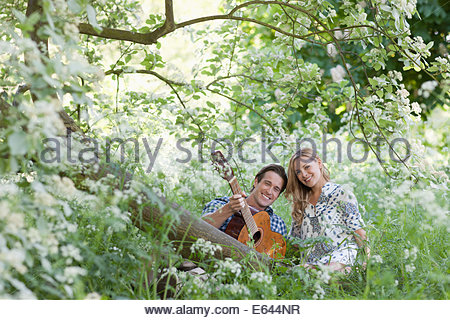 Man playing guitar for girlfriend in forest - Stock Photo
