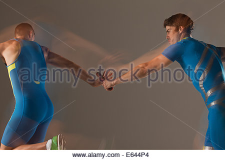 Blurred view of athletes passing baton - Stock Photo