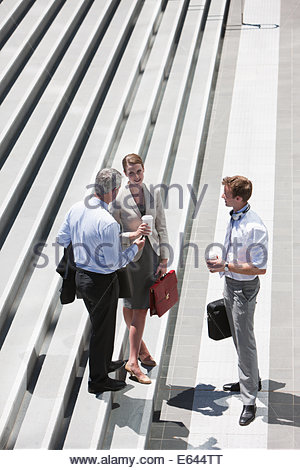Business people standing on steps outdoors - Stock Photo