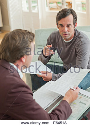 Man meeting with financial advisor in living room - Stock Photo