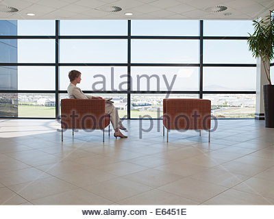 Businesswoman waiting in office waiting area - Stock Photo