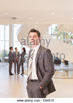 Businessman standing in office lobby - Stock Photo