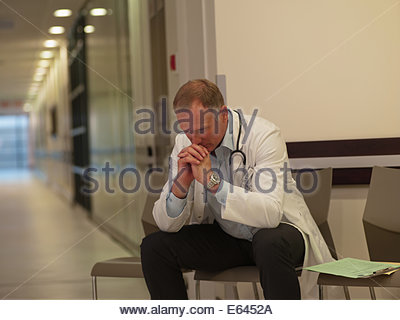 Frustrated doctor sitting in hospital waiting area - Stock Photo