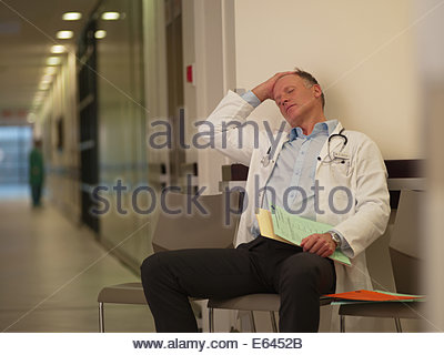 Tired doctor sitting in hospital waiting area - Stock Photo