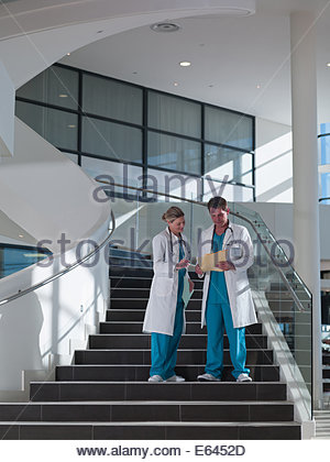 Doctors walking down staircase in hospital - Stock Photo