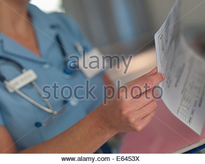 Nurse looking at patientÂ's medical chart - Stock Photo