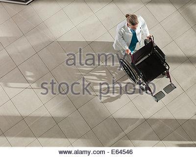 Doctor pushing wheelchair - Stock Photo
