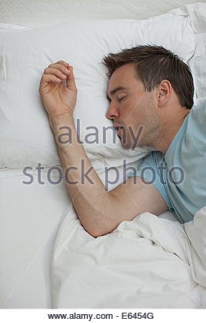 Sick man sleeping in bed - Stock Photo