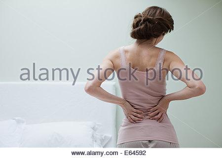 Woman rubbing aching back - Stock Photo