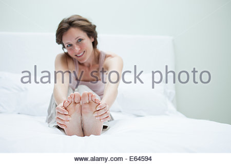 Smiling woman in bed holding feet - Stock Photo