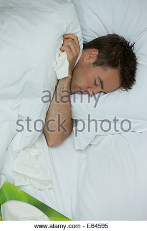 Close up of sick man sleeping in bed - Stock Photo