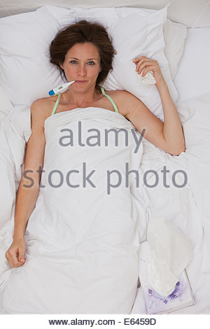 Sick woman taking temperature with digital thermometer - Stock Photo
