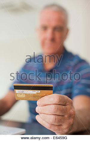 Man using credit card to purchase merchandise online - Stock Photo
