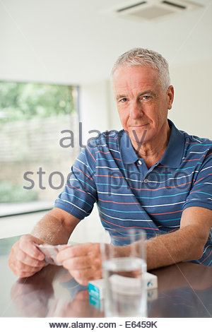 Man holding pills with glass at table - Stock Photo