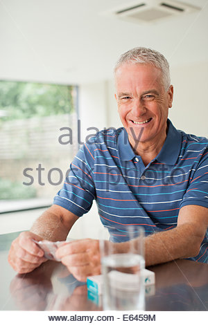 Happy man holding with glass at table - Stock Photo