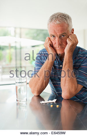 Unhappy man looking at pills on counter - Stock Photo