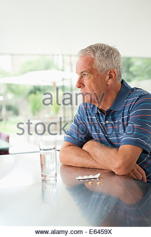 Unhappy man looking outside with pills on counter - Stock Photo