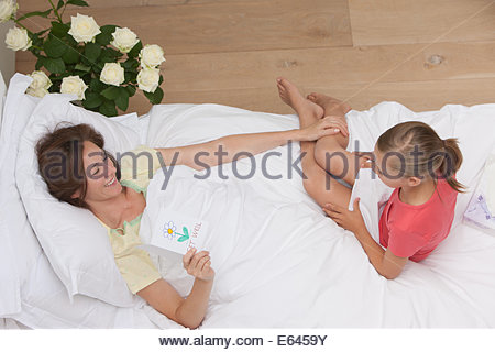 Mother laying in bed  with holding get well card - Stock Photo