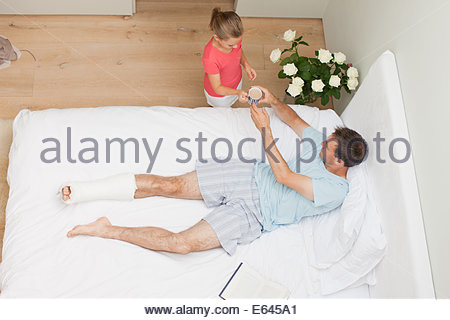 Daughter bringing coffee to father with broken leg - Stock Photo