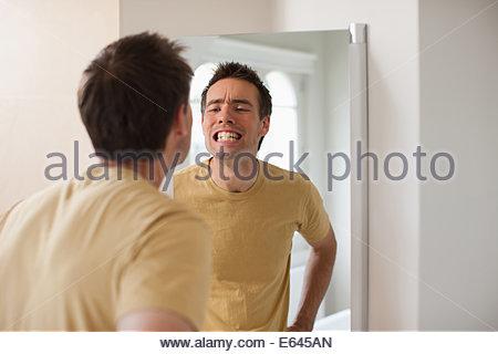 Man looking at teeth in mirror - Stock Photo