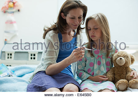 Mother checking daughterÂ's temperature with digital thermometer - Stock Photo