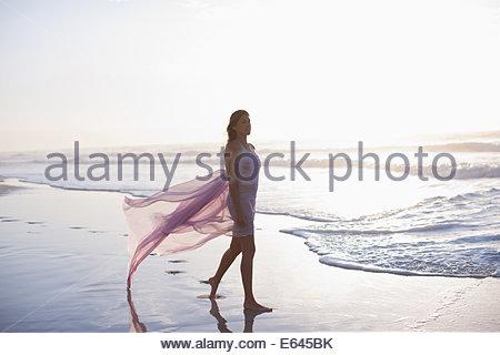 Woman walking on beach - Stock Photo