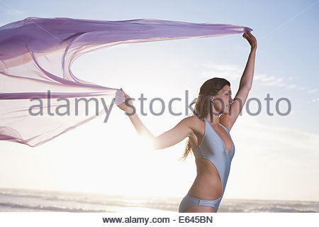 Woman holding sarong overhead on beach - Stock Photo