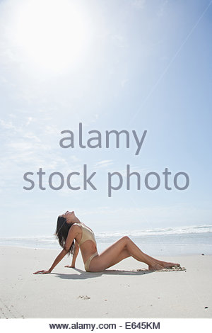 Woman in bathing suit sunbathing on beach - Stock Photo