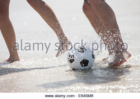 Friends playing football on beach - Stock Photo