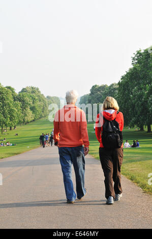 WINDSOR, UK - APRIL 24, 2011: Senior couple walk along the main alley in Windsor Great Park - Stock Photo