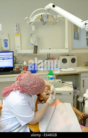 Young girl has her teeth cleaned by a dental hygienist at the dentist - Stock Photo