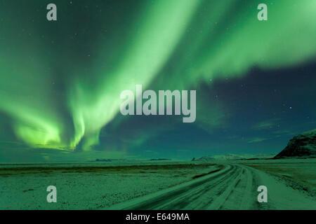 Northern Lights, Aurora Borealis, Winter road with snow, Iceland - Stock Photo