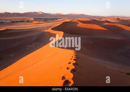 Middle aged man climbing sand dunes, Namib Naukluft National Park, Namibia - Stock Photo