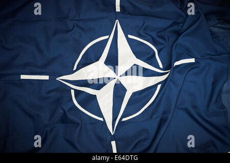 The flag of the North Atlantic Treaty Organization (NATO) consists of a dark blue field charged with a white compass - Stock Photo