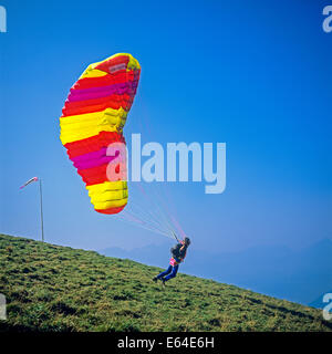 Paraglider taking off from top of Mont Chery Les Gets Savoy French Alps France - Stock Photo
