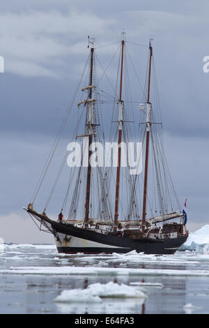 Black tourist sailing ship in Antarctic waters clogged with ice - Stock Photo