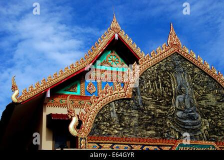 GEORGETOWN, MALAYSIA: Bas relief panel with Buddha and opulent roofs at Thai Wat Buppharam - Stock Photo