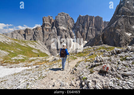 hiker on footpath  in Sella mountain, on background Mezdi valley and Piz da Lech peak, south Tyrol, Italy - Stock Photo