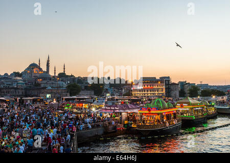 Hundreds of tourists and local Turks hang out along the Bosphorus as night comes on in Istanbul, Turkey. - Stock Photo