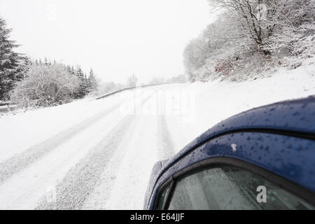 Car on a snowy country road in winter - Stock Photo