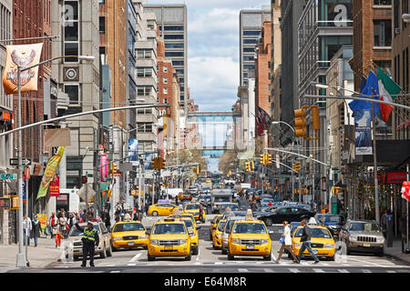Yellow Medallion taxi cabs waiting for green traffic light in Midtown Manhattan, New York, USA. - Stock Photo