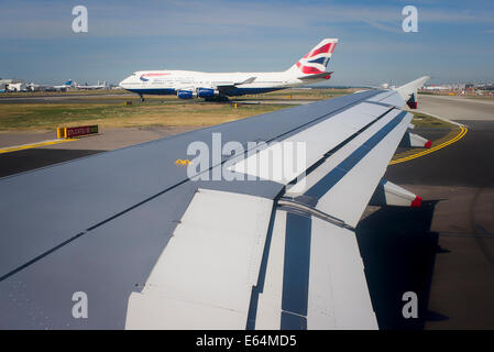 Wings of flight. View of airfileld with aircraft taxying in UK - Stock Photo