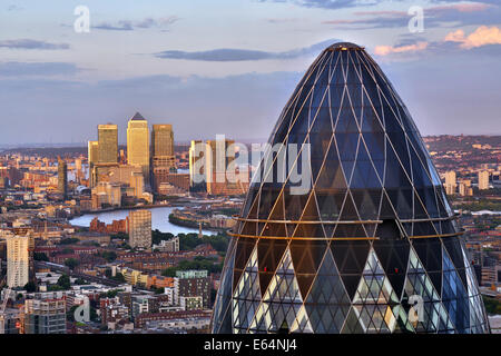 General view of buildings of the city skyline, Canary Wharf and the Gherkin, 30 St Mary Axe at dusk in London, England - Stock Photo